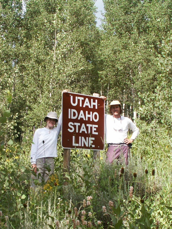 Jette Carr and Jon Warnick stand next to the sign stating they had crossed the Utah-Idaho state line, finishing their walk across the state, summer of 2003. The hike was part of a trek spanning from the bottom to the top of Utah to each boarder – a journey that took 43 days and was nearly 700 miles long.  (Courtesy photo)