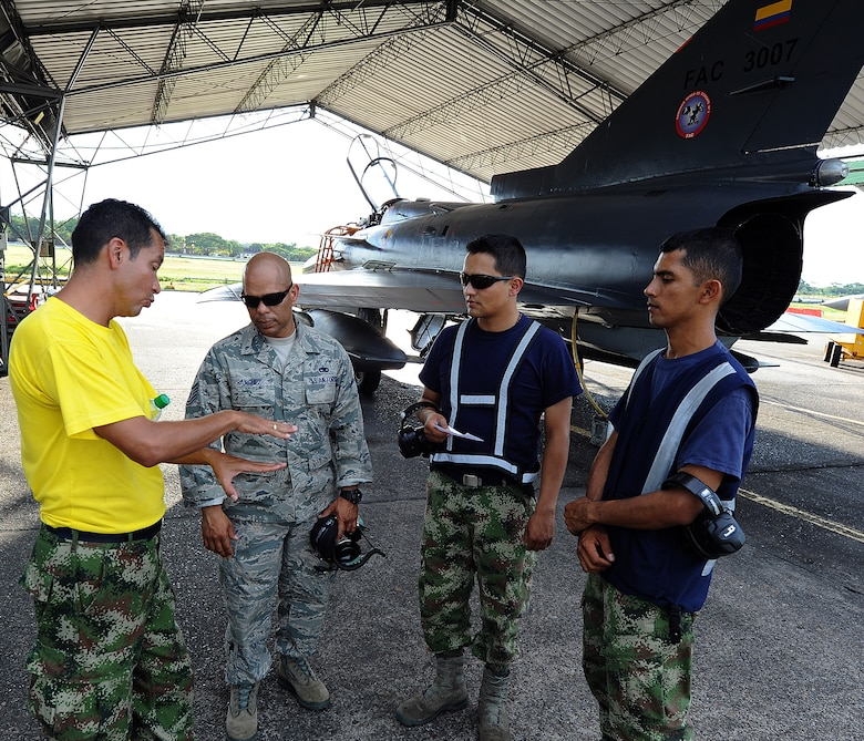 A Colombian air force crew chief explains to Tech. Sgt. Luis Sanchez, 571st MSAS aircraft maintenance air advisor, their aircraft launching procedures and communications with MOC prior to the evening's flights June 15, at Comando Aéreo de Combate No. 1 base, Palanquero, Colombia, as part of a month-long Air Mobility Command Building Partner Capacity mission. (U.S. Air Force photo by Tech. Sgt. Lesley Waters)