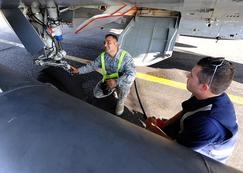 Master Sgt. Roberto Vasquez, 12th AF (AFSOUTH) heavy aircraft manager, and a Colombian crew chief inspect the wheels on a KFIR aircraft prior to take-off June 15, at Comando Aéreo de Combate No. 1 base, Palanquero, Colombia, as part of a month-long Air Mobility Command Building Partner Capacity mission. (U.S. Air Force photo by Tech. Sgt. Lesley Waters)