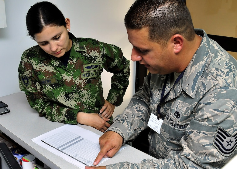 Technical Sgt. Melvin Rosario, Inter-American Air Forces Academy instructor, explains to 1st Lt. Mayra Moreno, CACOM-1 maintenance officer, how to read the evening's flight plan June 15, at Comando Aéreo de Combate No. 1 base, Palanquero, Colombia, as part of a month-long Air Mobility Command Building Partner Capacity mission. (U.S. Air Force photo by Tech. Sgt. Lesley Waters)