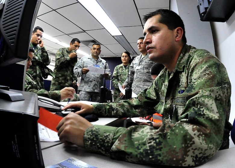 Master Sgt. Roberto Vasquez, 12th AF (AFSOUTH) heavy aircraft manager, and Technical Sgt. Melvin Rosario, Inter-American Air Forces Academy instructor, listen in as members of the Colombian air force maintenance operations centers go over the evening's flight schedule before the MOC briefing for senior leadership June 15, at Comando Aéreo de Combate No. 1 base, Palanquero, Colombia, as part of a month-long Air Mobility Command Building Partner Capacity mission. (U.S. Air Force photo by Tech. Sgt. Lesley Waters)
