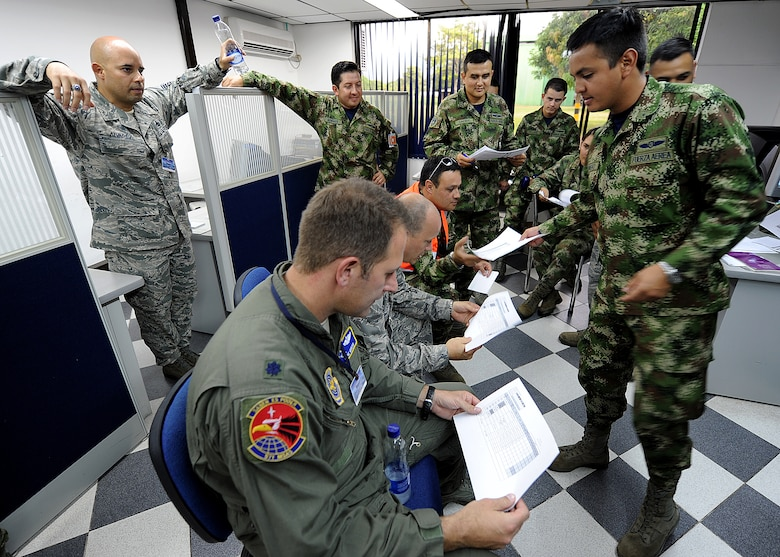 A Colombian air force member hands out the flight plan for the evening operations during the maintenance operations center briefing for senior leadership June 14, at Comando Aéreo de Combate No. 1 base, Palanquero, Colombia, as part of a month-long Air Mobility Command Building Partner Capacity mission. (U.S. Air Force photo by Tech. Sgt. Lesley Waters)