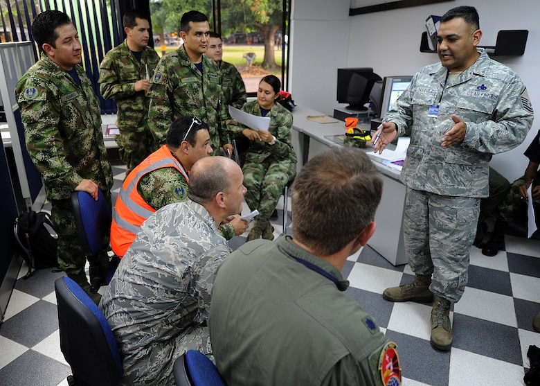 Master Sgt. Roberto Vasquez, 12th AF (AFSOUTH) heavy aircraft manager, shows the Colombian air force the proper way of providing a maintenance operations center briefing to senior leadership June 14, at Comando Aéreo de Combate No. 1 base, Palanquero, Colombia, as part of a month-long Air Mobility Command Building Partner Capacity mission. (U.S. Air Force photo by Tech. Sgt. Lesley Waters)