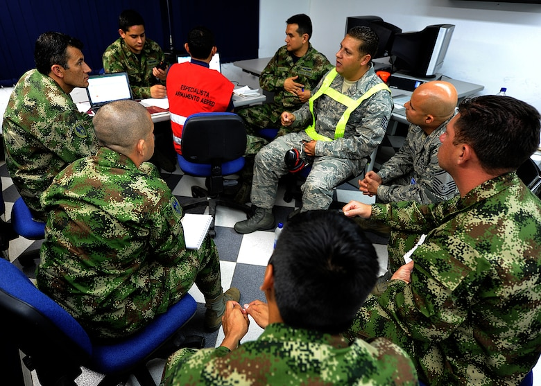 Technical Sgt. Melvin Rosario, Inter-American Air Forces Academy instructor, discusses maintenance operations center procedures to members of the Colombian air force June 13, at Comando Aéreo de Combate No. 1 base, Palanquero, Colombia, as part of a month-long Air Mobility Command Building Partner Capacity mission. (U.S. Air Force photo by Tech. Sgt. Lesley Waters)