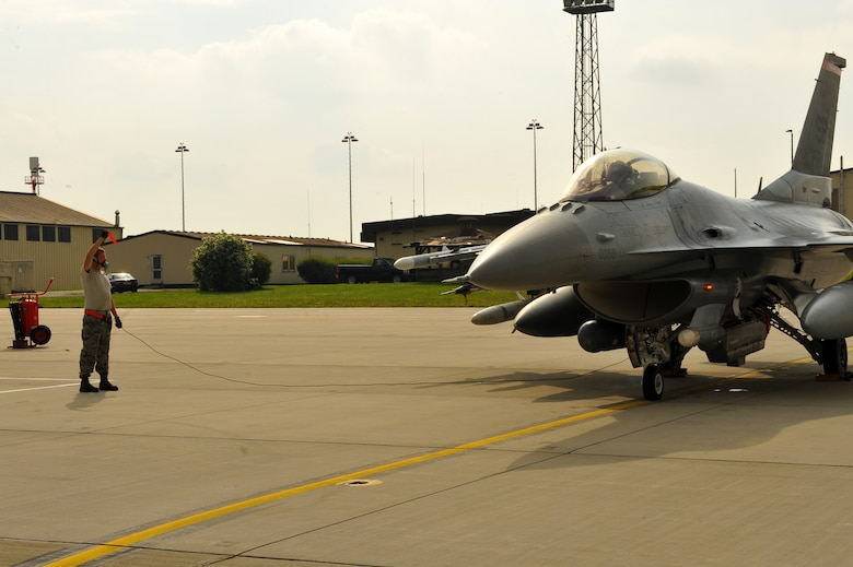 SPANGDAHLEM AIR BASE, Germany – Airman 1st Class Joshua Berard, 480th Aircraft Maintenance Unit crew chief, completes a standard aircraft launch procedure for an F-16 Fighting Falcon on Ramp 4 here June 19. The 480th AMU plays a vital role in supporting the F-16's combat training mission, which prepares them for regional defense and air superiority. (U.S. Air Force photo by Airman 1st Class Dillon/Released)