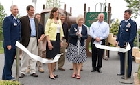 Suzie Schwartz, wife of Air Force Chief of Staff Gen. Norton Schwartz, cuts the ribbon at a ceremony unveiling a playground at the Fisher House for Families of the Fallen, Dover Air Force Base, Del., June 18, 2012. A need for a playground was made possible by the generosity of companies in the local community and across the nation. (U.S. Air Force photo/Roland Balik)
