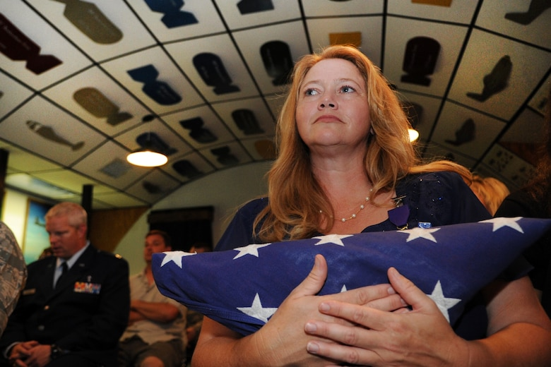 Cornelia Brantley holds the flag presented to her husband Chief Master Sgt. John Brantley during his retirement ceremony, May 18, 2012, at Barksdale Air Force Base, La. As a 24-year military spouse, she endured many separations and raised four children as her loved one served around the world. Now, two of her kids are also serving in the Air Force. (U.S. Air Force photo/Senior Airman Brigitte N. Brantley)