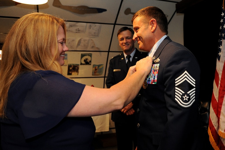 Cornelia Brantley, right, affixes a retirement pin to Chief Master Sgt. John Brantley's lapel during his retirement ceremony as his brother-in-law, retired Col. Randy Borg presides, May 18, 2012, at Barksdale Air Force Base, La. During their 24-year marriage, the couple has made it through some of the most difficult situations the military can present to family members. (U.S. Air Force photo/Senior Airman Brigitte N. Brantley)