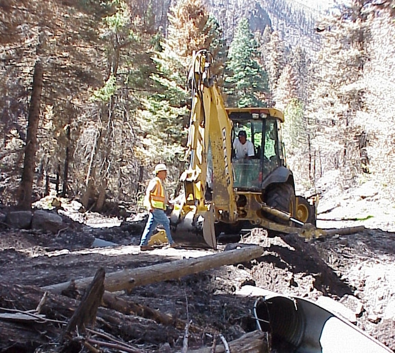 Joseph Lopez and Roger Apodaca, District's Abiquiu Lake equipment operators, narrowly escaped a flash flood while steadily maneuvering heavy equipment owned by the Corps to help clear debris from a flooded area of Santa Clara Canyon.