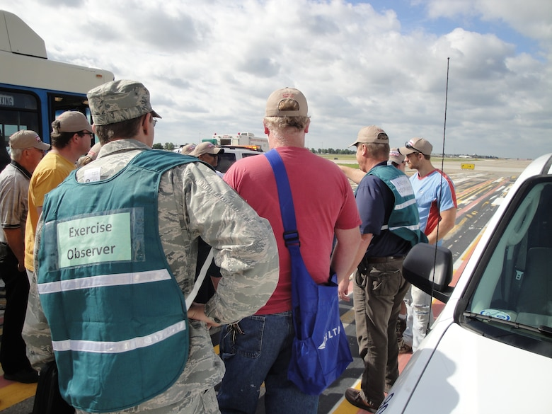 Senior Master Sgt. Brian Jansen, fire chief for the Missouri Air National Guard's 139th Airlift Wing, observes emergency responders, role players and city officials prepare for a major accident response exercise at Kansas City International Airport, Mo., June 20. The Wing provided a C-130 aircraft for use in the exercise. (Photo by Master Sgt. Mike R. Smith/Missouri Air Guard) (Released)