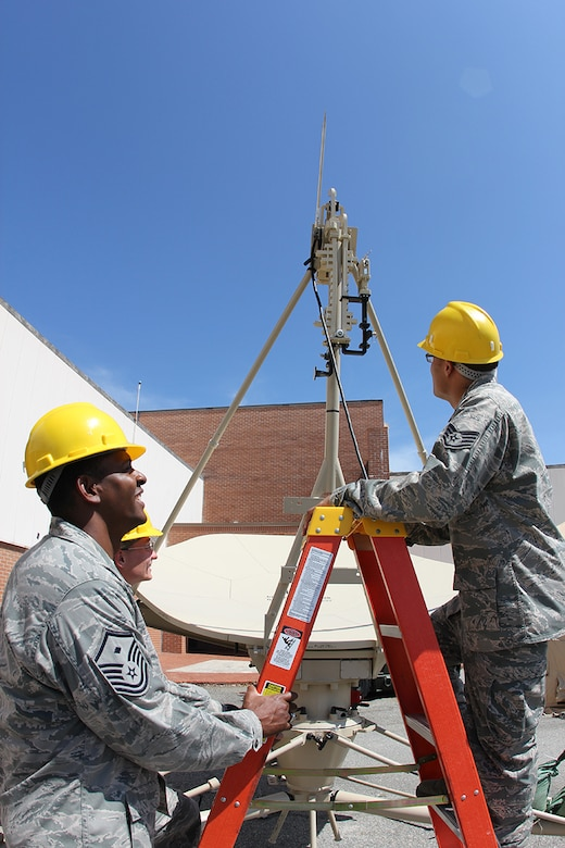 Master Sgt. H. Mylo Gibson II, 51st Combat Communications Squadron first sergeant, holds a ladder while Staff Sgt. Michael Joyner and Airman 1st Class Charles Haas, both 51st Combat Communications Squadron Radio Frequency transmission systems maintainers, inspect a ground multiband terminal. Gibson was selected as the Air Force's 2012 First Sergeant of the Year. (U.S. Air Force photo by Robert Talenti)