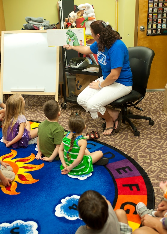 Erin Pearson, 23d Force Support Squadron head library clerk and storyteller, reads a picture book to children in the storytelling room at the library June 20, 2012, at Moody Air Force Base, Ga. Story time is part of the Summer Reading Program, which encourages children to continue reading over the summer. (U.S. Air Force photo by Airman 1st Class Jarrod Grammel/Released)