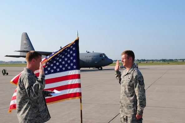 Tech. Sgt. Roman Jeter, C-130 Aircraft Crew Chief reenlists for six more years with the 107th Airlift Wing. Lt. Col. Christopher Thurn, 107th Airlift Wing's Maintenance Squadron Commander, performed the reenlistment oath on June 20, 2012. (U. S. Air Force Photo/Senior Master Sgt. Ray Lloyd)