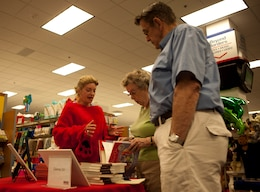 A couple checks out the works of Glenna C. Orr during a book fair at the Marine Corps Exchange aboard Marine Corps Base Camp Lejeune June 16. Orr has authored two books and is releasing a third in September.