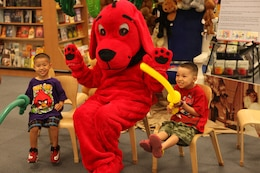 Two boys pose for a picture with author Glenna C. Orr dressed as Clifford the Big Red Dog during a book fair at the Marine Corps Exchange aboard Marine Corps Base Camp Lejeune June 16. Children were attracted to the bright red costume and kept visiting Orr throughout the day to hear her read some of her stories.