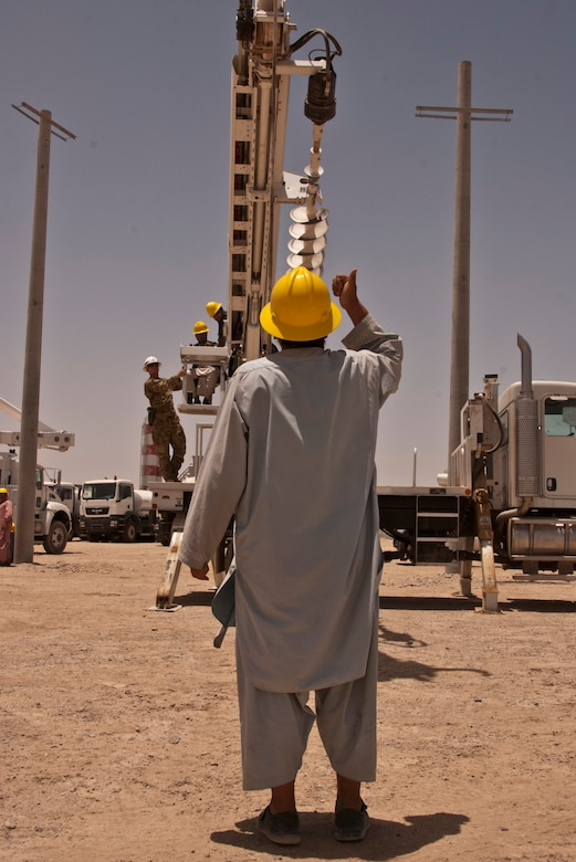 KANDAHAR AIRFIELD, Afghanistan — An Afghan electrical technicians practice hand signals while a fellow student learns how to operate a truck-mounted augur system used to emplace utility poles during a 10-day class led by the U.S. Army Corps of Engineers South District's non commissioned officers, June 10-19 2012.