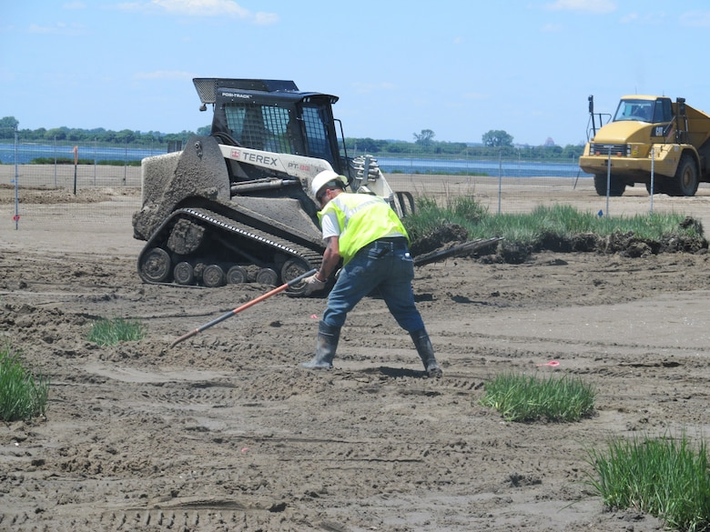 NEW YORK — A Burke Environmental contractor working on the site, finalizing the re-planting of a hummock. He is back filling dirt around the plant and then he will rake the area around it until it is smooth.