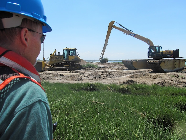 NEW YORK — Project Stakeholder from the New York State Department of Environmental Conservation watches hummock removal process.