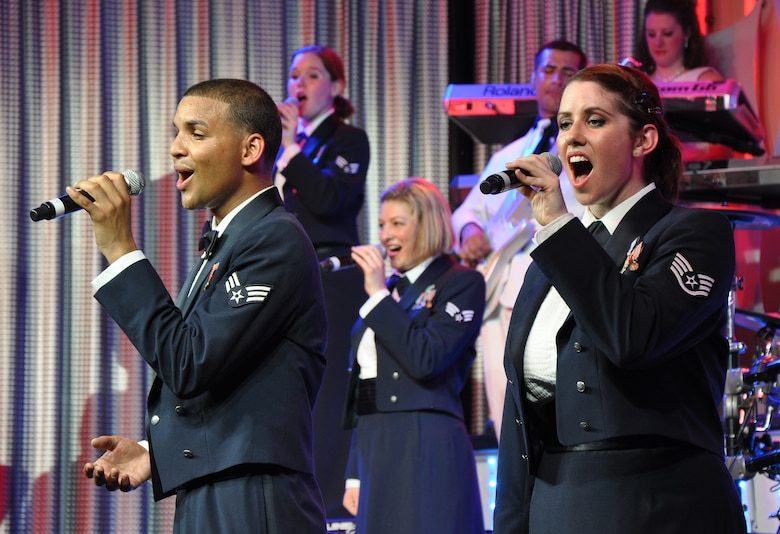Senior Airman Emmanuel Maldonado Rosario and Staff Sgt. Robin Elrod, Tops in Blue Vocalists, sing at Beale Air Force Base, Calif., June 16, 2012. TIB is composed of 35 to 40 vocalists, musicians, dancers, and technicians. (U.S. Air Force photo by Staff Sgt. Robert M. Trujillo/Released)