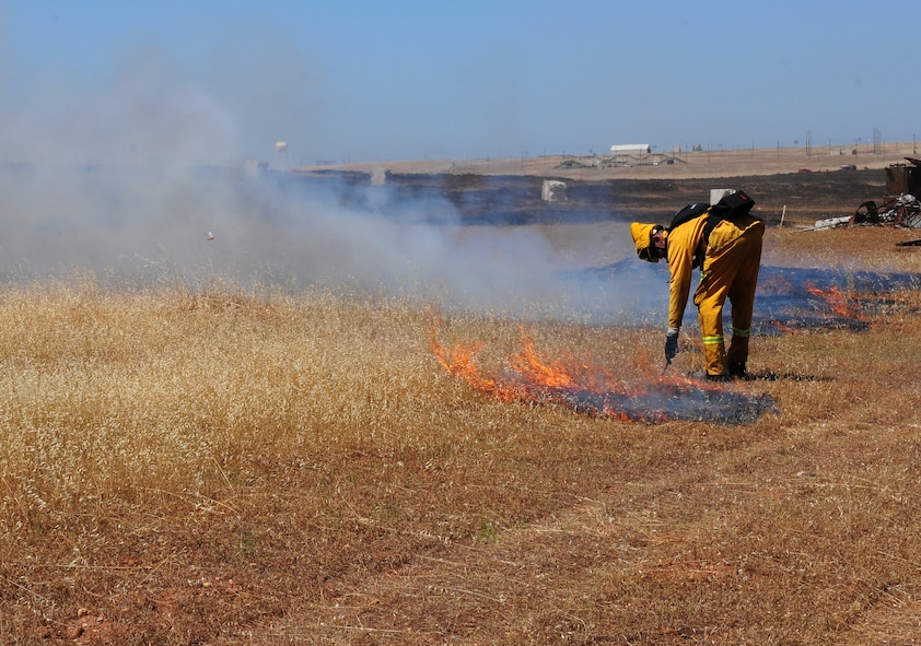Airman 1st Class Sean Russell, 9th Civil Engineering Squadron firefighter, uses a flare to burn the remaining unburned patches of grassland during the prescribed burn of the M60 machine gun range at Beale Air Force Base, Calif., June 19, 2012. Team Beale firefighters often support local fire departments during the fire season. (U.S. Air Force photo by Senior Airman Allen Pollard/Released)
