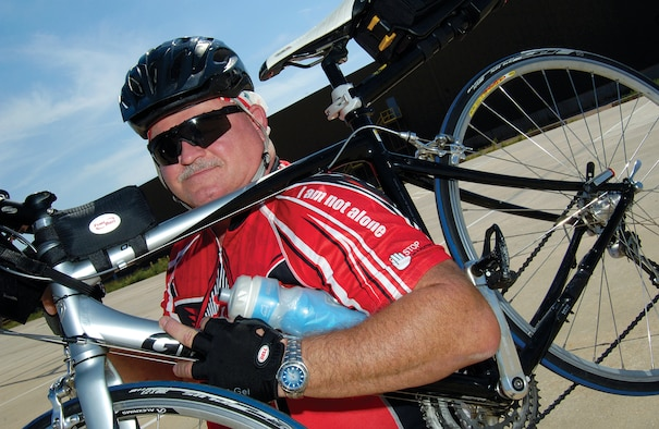 Dave Thomas, of the Defense Logistics Agency, Oklahoma City, often rides his bike to work at Tinker, wearing a high-visibility red shirt that brightly testifies to his war on diabetes and his passion to educate others while helping control the disease in his own life. (Air Force photo by Margo Wright)