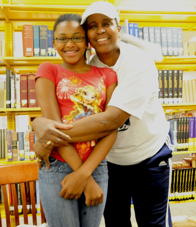 Donna Moore, Air Force retiree, embraces her daughter Jazymn Brown Washington during opening day of the Summer Reading program at the library at Joint Base Andrews Library on June 18. The Summer Reading program motivates, inspires and teaches individuals of all ages to read as much as possible. (U.S. Air Force Photo/Senior Airman Amber Russell)