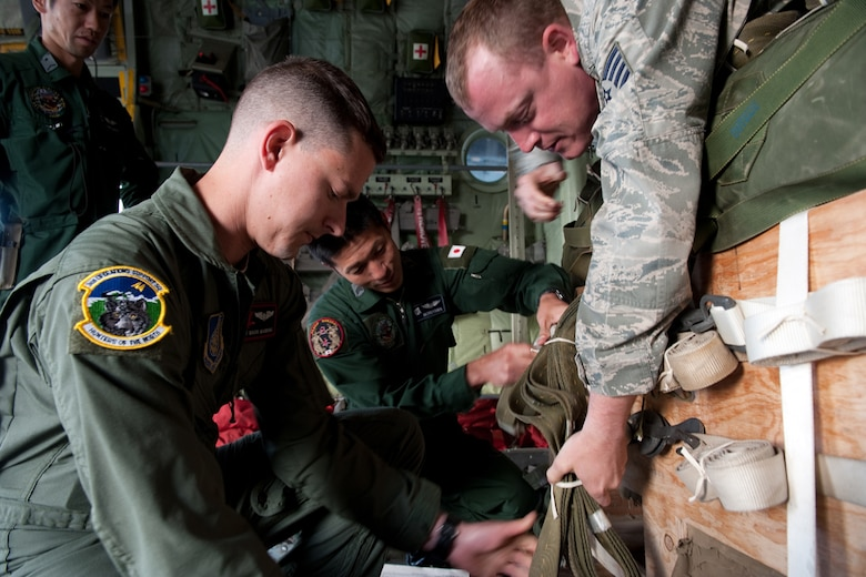 U.S. Air Force Staff Sgt. Mark Manning, front left, and TSgt Michael Dunkelberger, front right, examine the air drop system with members of the Japanese Air Self Defense Force during pre-flight inspections for the Japanese C-130 Hercules during Red Flag - Alaska on the flight line of Joint Base Elmendorf-Richardson, Alaska June 19. The C-130 Hercules offers a maximum speed of 600 kilometers an hour with a payload of 19,400 pounds and can be used for air drops. Red-Flag Alaska is designed to strengthen bilateral ties between nations and offers the JASDF the opportunity to improve aerial tactics. (U.S. Air Force photo/Staff Sgt. Robert Barnett)