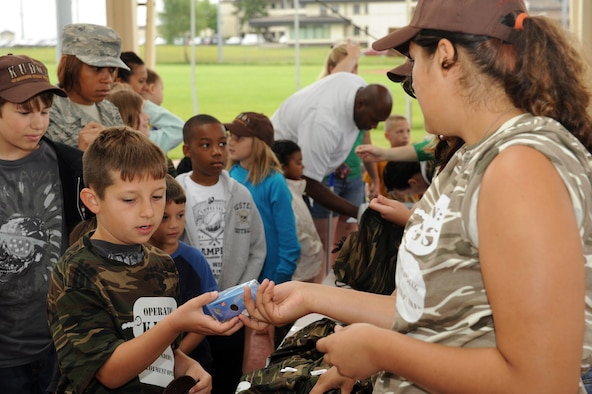 SPANGDAHLEM AIR BASE Germany-- Kirsten Hooper,right, daughter of Staff Sgt. Timothy Gallagher, 52nd Component Maintenance Squadron, hands out cameras during Children Deployment Day at the outdoor basketball court here June 21. Volunteers issued children ID cards, shirts, hats, cameras, activity books and a deployment bag. The event gave children the opportunity to experience different stages of the deployment process. (U.S. Air Force photo by Senior Airman Christopher Toon/Released)