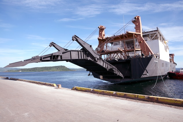 The ramp of the USNS Sgt Mate Kocak lowers during an off-load/cross-leveling operation to retrograde equipment into the caves, belonging to the Marine Corps Prepositioning Program-Norway.  During this operation more than 150 vehicles and 200 shipping containers were transferred on or off the Kocak and staged for transportation to the caves or loaded back onto the ship. The MCPP-N facility is comprised of eight locations totaling more than 900,000 square feet of storage space. Inside the caves is  471,445 sq. ft. of climate controlled storage space, regulated to between 45 to 55 percent humidity and a regulated temperature of between 45 to 50 degrees. This precise regulation allow for tents, vehicle tires and parts and other climate sensitive equipment to be stored safely, and maintain a high level of accessibility to be readily deployable for any contingency that may arise.