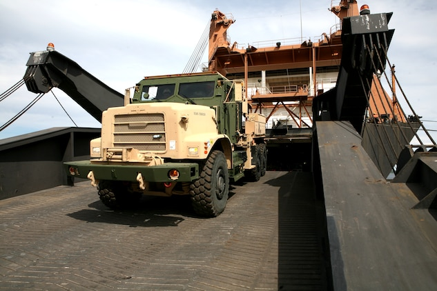 A Marine assigned to Combat Landing Brigade-13 drives a Medium Tactical Vehicle Replacement (MTVR) down the ramp of the USNS Sgt Mate  Kocak during an off-load/cross-leveling operation to retrograde equipment into the caves, belonging to the Marine Corps Prepositioning Program-Norway.  During this operation more than 150 vehicles and 200 shipping containers were transferred on or off the Kocak and staged for transportation to the caves or loaded back onto the ship. The MCPP-N facility is comprised of eight locations totaling more than 900,000 square feet of storage space. Inside the caves is  471,445 sq. ft. of climate controlled storage space, regulated to between 45 to 55 percent humidity and a regulated temperature of between 45 to 50 degrees. This precise regulation allow for tents, vehicle tires and parts and other climate sensitive equipment to be stored safely, and maintain a high level of accessibility to be readily deployable for any contingency that may arise.