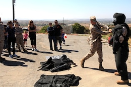 Marines of Security Battalion demonstrate the effectiveness of the Fist Suit by swinging a metal bar at the suit during the Jane Wayne Day on Camp Pendleton, June 23. The suit is used for riot control or to escort prisoners who may cause harm to themselves or others.