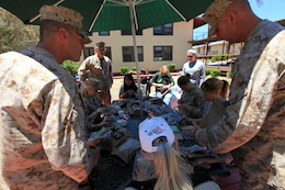 The Marines teach the spouses about Meals, Ready-to-Eat and how to prepare them for consumption during the Security Battalion's Jane Wayne Day on Camp Pendleton, June 23. After lunch, Col. Gino P. Amoroso and Sgt. Maj. Kenneth E. Warren presented each spouse with a certificate for participating in Jane Wayne Day. Amoroso is the commanding officer