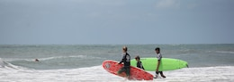 Two Indo Jax surf instructors head into the water at Onslow Beach aboard Marine Corps Base Camp Lejeune, June 15. Indo Jax holds summer camps for youth as well as group classes and individual classes for adults.