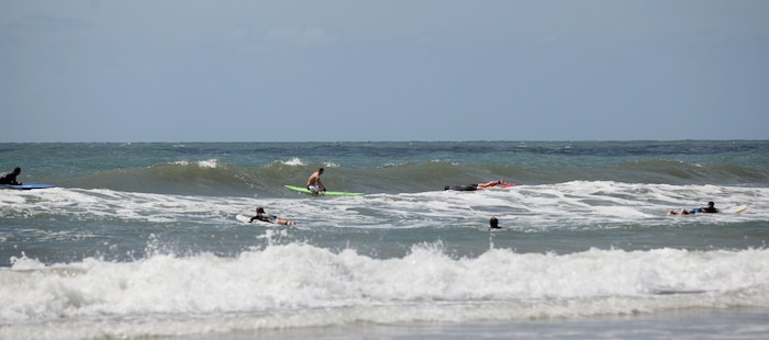 Wa Lu Warriors and their instructors paddle through the waves at Onslow Beach aboard Marine Corps Base Cmap Lejeune, June 15. The Ma Lu Warriors are wounded warriors who enjoy the therapeutic aspects of surfing.