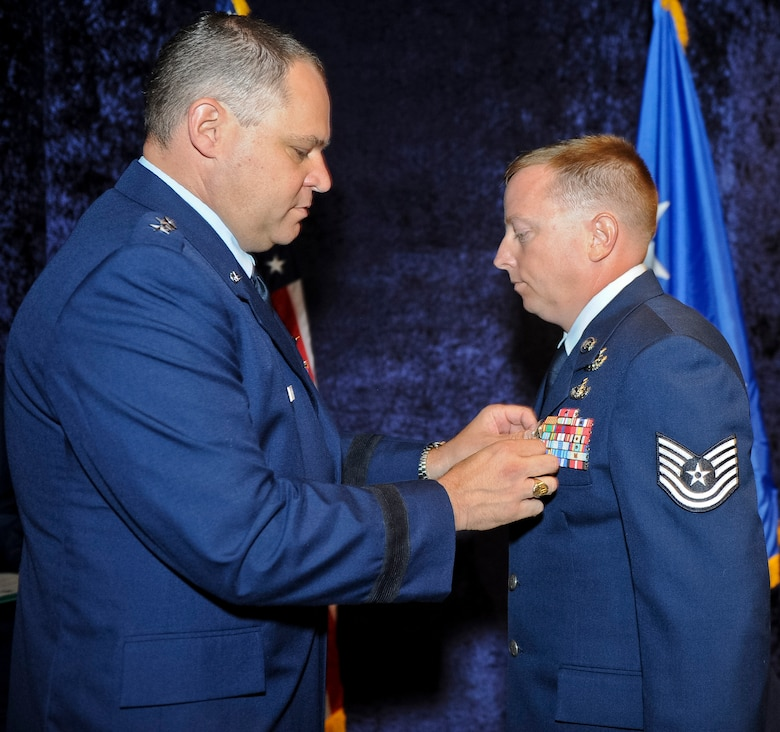 Maj. Gen. Jim Butterworth, Georgia National Guard adjutant general, pins a Bronze Star Medal on Tech. Sgt. Barry Duffield, 116th Civil Engineering Squadron explosive ordnance technician, during a ceremony at the Museum of Aviation, Robins Air Force Base, Ga., June 18, 2012.  Duffield received the medal, his 2nd, for his achievements while serving as an explosive ordnance disposal team leader in Afghanistan during a six-month period from 2011 to 2012.  ( National Guard photo by Master Sgt. Roger Parsons/Released)
