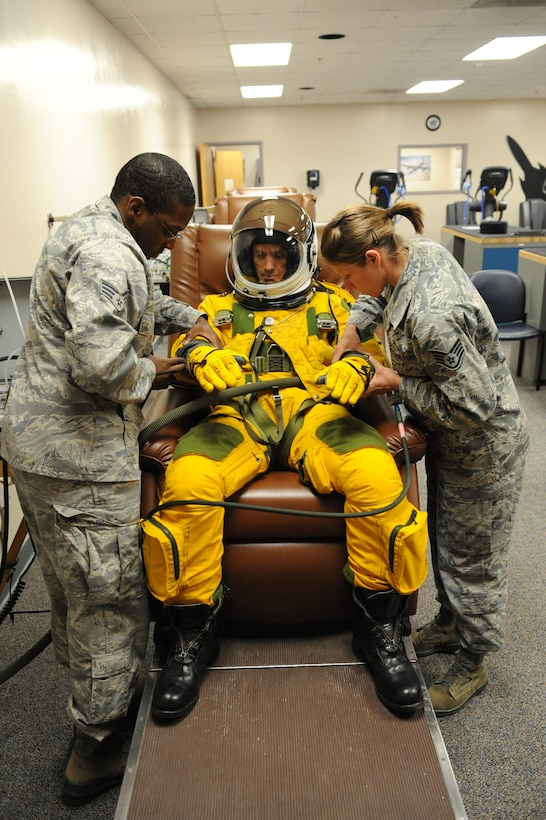 (Left) Senior Airman Michael Gaines and (right) Staff Sgt. Tara Schmidt, , 9th Physiological Support Squadron life support technicians, dress Chief Masters Sgt. Richard Parsons, command chief of Air Combat Command, in a U-2 Dragon Lady pressure suit at the 9th PSPTS integration room June 21, 2012 at Beale Air Force Base, Calif.  Parsons was visiting base facilities and meeting Airmen from units and organizations responsible for accomplishing the mission of the 9th Reconnaissance Wing and tenant units. (U.S. Air Force photo by Mr. John Schwab)