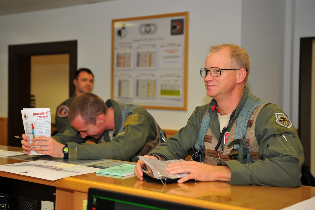 SPANGDAHLEM AIR BASE, Germany – Brig. Gen. Chris Weggeman, right, 52nd Fighter Wing commander, goes through a briefing to gather weather and flight information at the 480th Fighter Squadron operations desk here June 21 before his final F-16 Fighting Falcon launch. Weggeman commanded the 52nd FW for two years. (U.S. Air Force photo by Airman 1st Class Dillon Davis/Released)