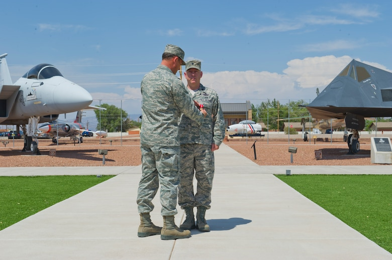 Colonel David Krumm, 49th Wing commander, pins the Bronze Star Medal on Lt. Col. Thomas McCurley, Detachment 2, Air Combat Command Training Support Squadron commander, at the Holloman Air Force Base, N.M., Heritage Park June 15. According to his award citation, McCurley was awarded the Bronze Star for providing superb leadership as the 60th Expeditionary Reconnaissance Squadron's first commander, enabling critical intelligence collection, and precise on-call strike capabilities in support of special operations forces ground commanders. McCurley's late grandfather also received a Bronze Star for his actions during the Invasion of Normandy in 1944. (U.S. Air Force photo by Airman 1st Class Daniel E. Liddicoet/Released)