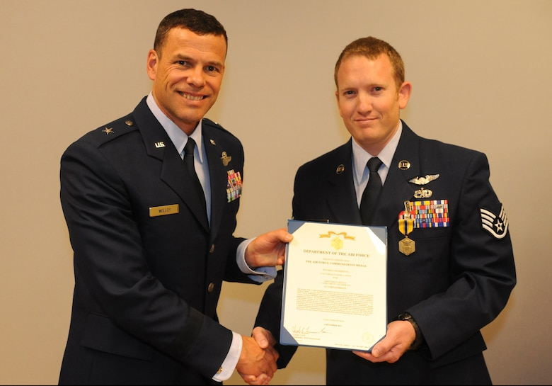 U.S. Air Force Staff Sgt. Mark Smith, 33rd Rescue Squadron, receives the Air Force Commendation Medal from Brig. Gen. Matthew Molloy, 18th Wing commander, at the 33rd RQS auditorium on Kadena Air Base, Japan, June 20, 2012. Smith was among seven 33rd RQS Airmen presented medals for various achievements including deployment actions in Afghanistan. (U.S. Air Force photo/Airman 1st Class Justin Veazie)