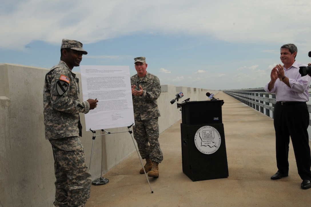 "LOUISIANA — Lt. Gen. Thomas Bostick, Commanding General of the U.S. Army Corps of Engineers, signed the ""Louisiana Coastal Area Barataria Basin Barrier Shoreline Restoration"" report June 22, 2012 on top of the Inner Harbor Navigation Canal Surge Barrier. Col. Edward Fleming, U.S. Army Corps of Engineers New Orleans District commander, highlighted the united front federal, state and local agencies are taking in support of the Hurricane and Storm Damage Risk Reduction System building built here. The HSDRRS system is referred to as the best the area has ever had regarding storm risk reduction. On hand for the ceremony was U.S. Sen. David Vitter."