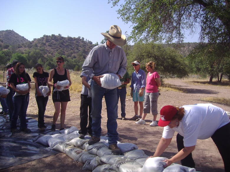 The prepared sandbags are stacked by participating community members.