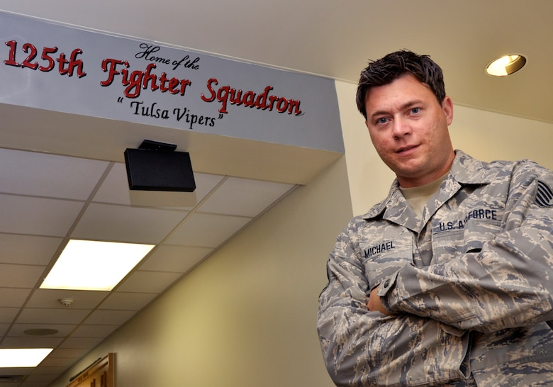 Technical Sergeant Michael T. Craig, 138th Fighter Wing Aircrew Flight Equipment Specialist, stands beside one of his artistic endeavors at the flight operations entrance at the 125th Fighter Squadron, Oklahoma Air National Guard, Tulsa, OK.  TSgt Craig has been adorning the facility with his work since he joined the unit in September 2008.