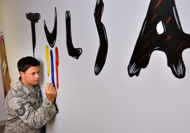 Technical Sergeant Michael T. Craig, 138th Fighter Wing Aircrew Flight Equipment Specialist, touches up some his art work that leads into his work area at the 125th Fighter Squadron, Oklahoma Air National Guard, Tulsa, OK.  TSgt Craig has been adorning the facility with his work since he joined the unit in September 2008.