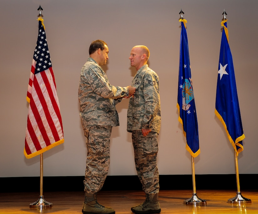 Staff Sgt. Douglas Ryan, 628th Explosive Ordnance Disposal noncommissioned officer in charge of training, stands at attention while Maj. Gen. Timothy Byers, the Air Force Civil Engineer, pins on one of his two medals he received June 27 at the Joint Base Charleston Theater. Ryan deployed once to Iraq and twice to Afghanistan. In addition to the Air Force Combat Action Medal and Bronze Star, he has also received the Army Combat Action Badge and the Navy/Marines Corps Combat Action Ribbon as well as multiple Army Commendation medals. (U.S. Air Force photo by Airman 1st Class Chacarra Walker/Released)