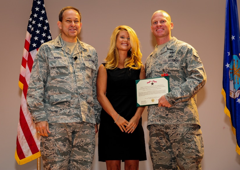 Major Gen. Timothy Byers, the Air Force Civil Engineer, Staff Sgt. Douglas Ryan, 628th Explosive Ordnance Disposal noncommissioned officer in charge of training and his wife Becka Ryan pose for a photo after Ryan was presented with the Air Force Combat Action Medal and the Bronze Star Medal June 27 at the Joint Base Charleston Theater. Ryan deployed once to Iraq and twice to Afghanistan. In addition to the Air Force Combat Action Medal and Bronze Star, he has also received the Army Combat Action Badge and the Navy/Marines Corps Combat Action Ribbon as well as multiple Army Commendation medals. (U.S. Air Force photo by Airman 1st Class Chacarra Walker/Released)