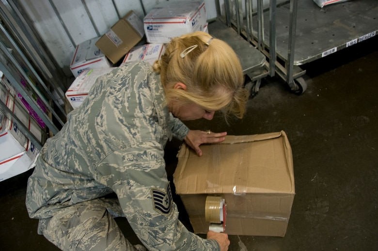 Technical Sgt. Loreen Fetterhoff, 379th ECS official mail manager, reseals a package June 27, 2012 at the Blatchford-Preston Complex Post Office. The post office staff ships between 200 and 300 parcels every day. (U.S. Air Force photo/Senior Airman Bryan Swink)