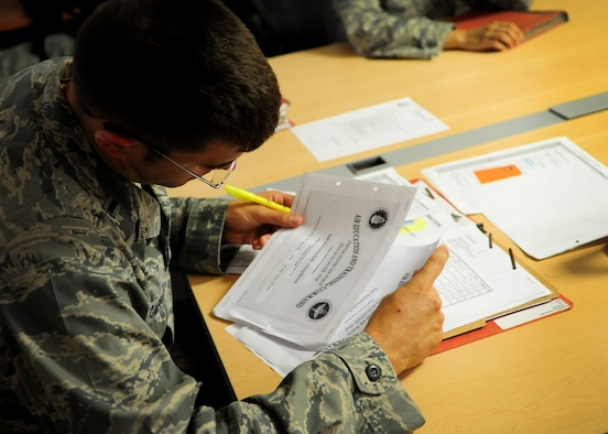 In preparation for a simulated deployment as part of a local readiness exercise, 1st Lt. Gregory D. Cappuzzo, 31st Comptroller Squadron, reviews a fellow squadron member's mobility folder at Aviano Air Base June 18. Servicemembers currently in their air and space expeditionary force band are required to ensure they have up-to-date records and training to support contingencies at a moment's notice. (U.S. Air Force photo/Staff Sgt. Evelyn Chavez)