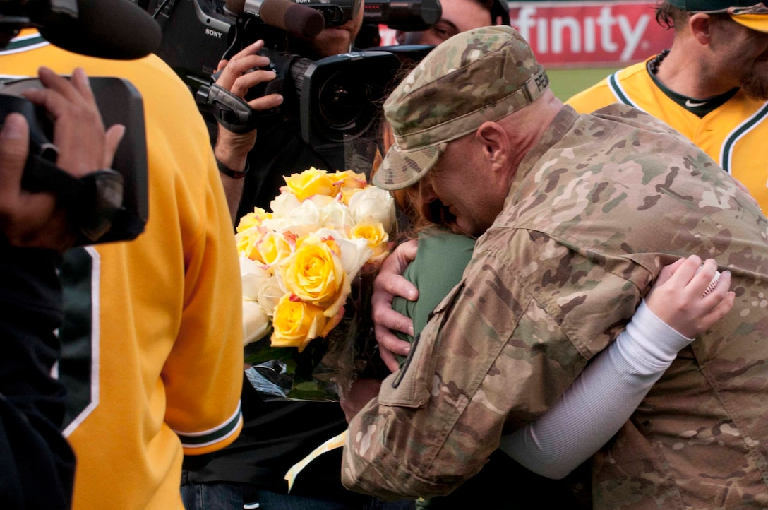 OAKLAND, Calif. — Allie Pearce gets a hug from her dad, Army Specialist Scott Pearce, before the Oakland Athletics game against the San Francisco Giants at O.co Coliseum here, June 22, 2012.