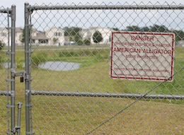 An alligator warning sign is posted on the chain-linked fence surrounding storm water pond aboard Marine Corps Base Camp Lejeune's Tarawa Terrace residential area. These fences also keep alligators from straying into residential areas where they can be a threat.