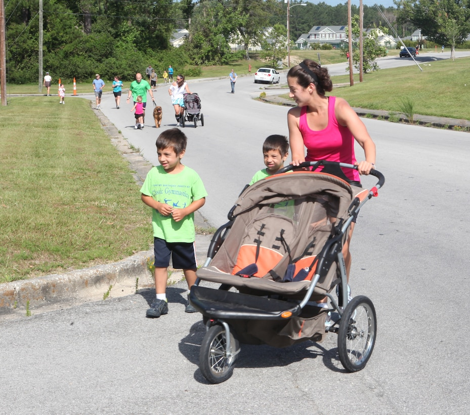 A mother and her sons finish the jogging route during the 80s-themed Family Fun Run hosted by the Tarawa Terrace Community Center aboard the MCB Camp Lejeune housing area recently. The 80s-themed run was the sixth run hosted this year and 150 runners of all ages attended the family occasion.